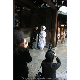 Japanese couple posing for both a professional photographer and a woman, after their wedding during a rainy day. Shinto temple, Tokyo, Japan