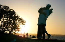 Sailor kissing nurse sculpture (from the photo by Alfred Eisenstaedt) at sunset with a man passing by. San Diego bay, California