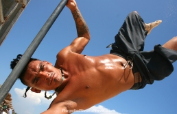 Young man practicing pole acrobatics in the beach during a sunny day. Playa del Carmen, Quintana Roo, México