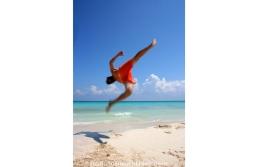 Young man practicing acrobatics in the beach, during a sunny day. Playa del Carmen, Quintana Roo, México