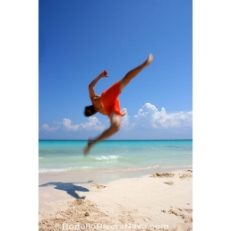 Young man practicing acrobatics in the beach, during a sunny day. Playa del Carmen, Quintana Roo, México