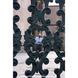 Senior man seen through an iron fence, in Chihuahua city Cathedral. Chihuahua, México