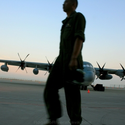 Training pilot passing by in front of military freight airplane. USA Air Force San Diego base, California