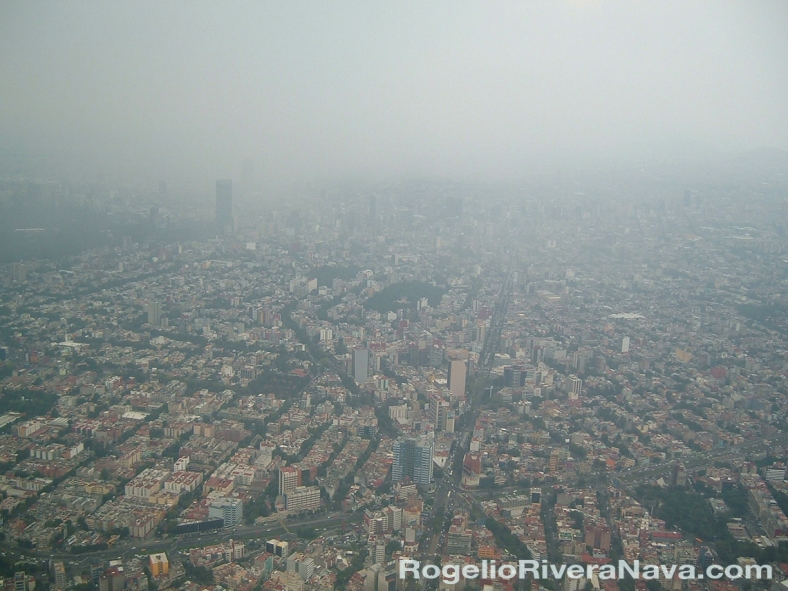 Aerial view of Mexico City (Ciudad de México) from an airplane showing severe air pollution. July 29, 2006. / Photo by: Rogelio Rivera-Nava / rogelioriveranava.com / [ Focal lenght: 5.7 | Shutter speed: 1/240 s | f number: 2.8 | No filter and no digital touching, only slight compensation for loss of light through aircraft window, with the use of CS6 Photoshop auto levels]